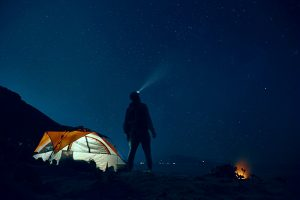 flashlight at night by tent